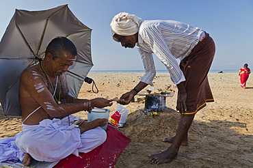 Local priest receiving money after leading a religious ceremony on the beach of Varkala, India, Asia