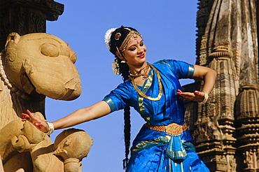 Odissi dancer posing in front of the Khajuraho temples, Khajuraho, Madhya Pradesh, India, Asia