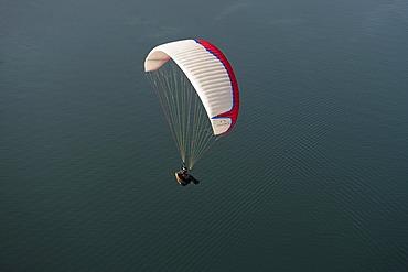 Paragliding, paraglider flying over Lake Garda, Veneto, Italy