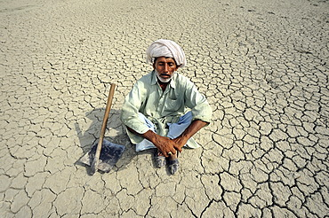 Farmer with closed eyes sitting on dried loamy soil, dreaming, Basti Lehar Walla village, Punjab, Pakistan, Asia