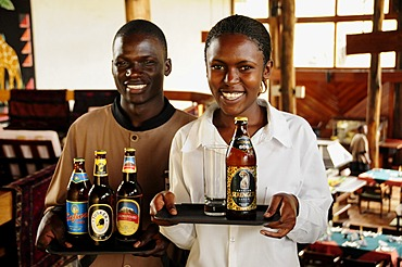 Waiter and waitress carrying the most popular beer brands in Tanzania, Serengeti, Kilimanjaro, Safari and Tusker, Lobo Wildlife Lodge, Serengeti National Park, Tanzania, Africa