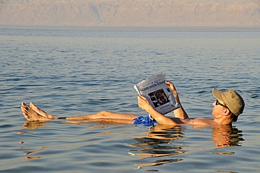 Tourist reading the newspaper in the Dead Sea, high salt content, near Suwaymah, Jordan, Middle East, Orient