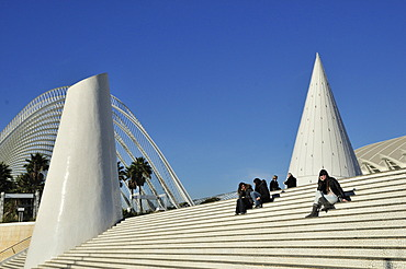 Tourists sitting on the steps of the Ciudad de las Artes y las Ciencias, City of Arts and Sciences, designed by Spanish architect Santiago Calatrava, Valencia, Comunidad Valenciana, Spain, Europe