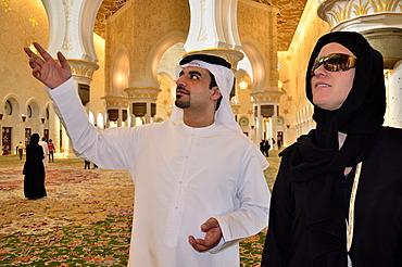 Local man giving veiled tourist a tour of the Sheikh Zayed Mosque, Abu Dhabi, United Arab Emirates, Arabian Peninsula, Asia