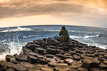 Man taking photo with a smartphone, Giant's Causeway, basalt columns, Causeway Coast, County Antrim, Northern Ireland, United Kingdom, Europe