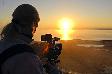 Camerawoman filming sunset, USA, United States of America