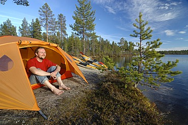 Man sitting in front of a tent at a lakeside, looking into the distance, Femundsmarka National Park, Femundsmark, Norway