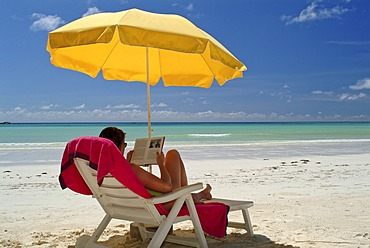 Woman sitting on deck chair under a yellow parasol, reading a book, Praslin Island, Seychelles, Africa
