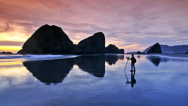 Camera woman with a film camera and tripod filming a sunset at Meyers Creek Beach, Pistol River State Park, Oregon coast, Oregon, USA, North America