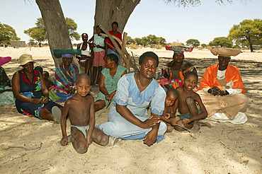 Locals sitting under village tree, Sehitwa, Botswana, Africa