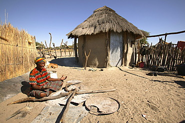 Woman sitting in front of a round-hut
