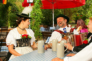 Couple wearing traditional costume in a beer garden, Muehldorf am Inn, Upper Bavaria, Germany, Europe