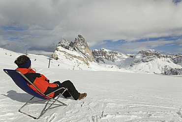 Man sitting in a deck chair on ski slope, Sella Massif, Dolomites, South Tyrol, Italy