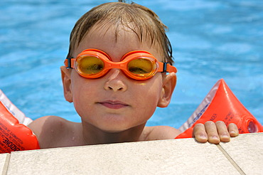 Boy in the water with diving goggles and water wings