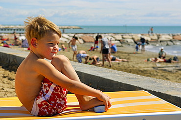 Boy sitting on a lounger on the beach, Caorle, Veneto, Italy