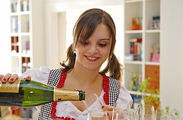 Young woman in dirndl, pouring champgane into a glass