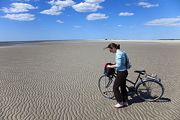 Woman walking barefoot with a bike on the widest beach in northern Europe, Havsand, island of Rømø, Tønder, Denmark, Europe