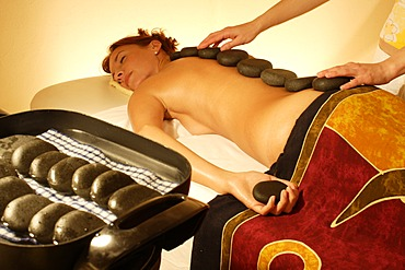 Massage therapist placing hot stones on client