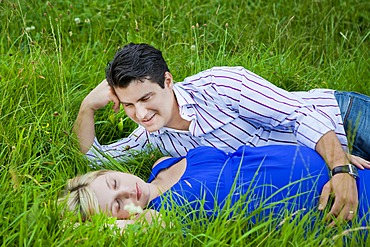 Man lying with his pregnant woman in the grass and looking at her tenderly