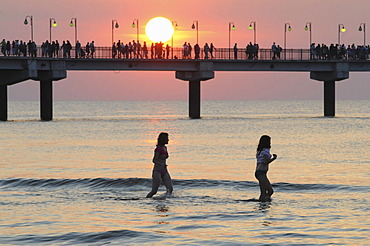 The pier in sunset and bathing girls, Miedzyzdroje, Poland, Europe