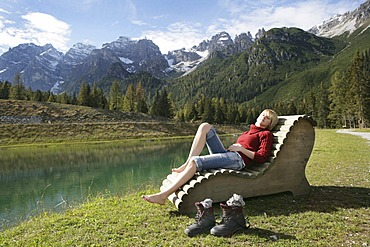 AUT, Austria, Fulpmes, Stubai Valley: Hiking path in the mountains to the Schlickeralm. Relaxing at the Speichersee lake on wooden chairs and beds. |
