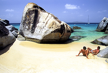 "Sunbathing couple, sailboat in the distance, ""The Baths, "" Virgin Gorda Island, British Virgin Islands, Lesser Antilles, Caribbean"
