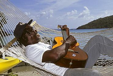Man laying in a hammock playing the guitar, Jost Van Dyke Island, British Virgin Islands, Lesser Antilles, Caribbean