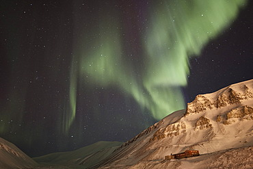 Strong green Northern Lights, Aurora Borealis, above a historic building lit by the lights of the town of Longyearbyen, Longyearbreen Glacier at back, Spitsbergen, Svalbard, Norway, Europe