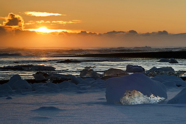 Sunset behind the snow-covered icebergs at the Atlantic coast near Joekulsarlon, Vatnajoekull National Park, Iceland, Europe