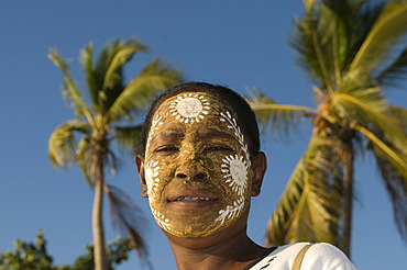 Portrait of smiling, dark-skinned woman with facial painting, Nosy Be, Madagascar, Africa