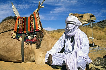 Tuareg man sitting beside his camel, Libya, North Africa