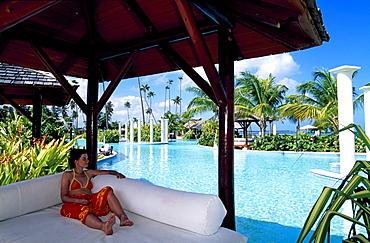 Woman relaxing beside the pool, Gran Melia Resort near Rio Grande, Puerto Rico, Caribbean
