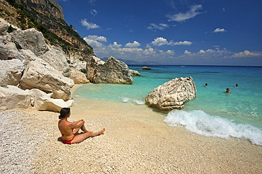 Woman lying on the beach, Cala Goloritze bay, Golfo di Orosei, Gennargentu National Park, Sardinia, Italy, Europe