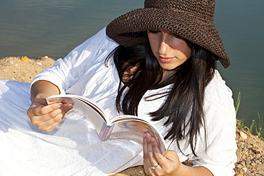 Young woman wearing a straw hat sitting on the beach of a quarry pond and reading a book