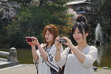 Japanese teenagers with blonde dyed hair, wearing the typical fashion taking photos in Maruyama Park, Kyoto, Japan, Asia