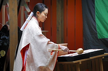 Shrine maiden handing out holy sake, rice wine, for the participants of the procession from the Shimogamo shrine to the Mikage shrine, Kyoto, Japan, Asia