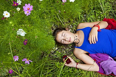 Girl, 11 years, lying in a flower meadow listening to music on an MP3 player