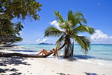 Woman lying on a coconut tree, Anse La Passe, Silhouette Island, Seychelles, Africa, Indian Ocean