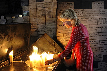 Woman lighting a candle in the Stone Gate (Kamenita vrata), a place of prayer for believers, Zagreb, Croatia