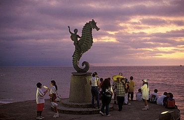 Tourists enjoying the sunset view beneath a statue of a person riding a seahorse on the beach promenade in Puerto Vallarta, Jalisco, Mexico