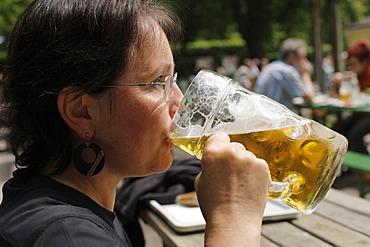 Woman drinking a litre of Spaten brand beer, Taxisgarten Beer Garden, Munich, Bavaria, Germany, Europe