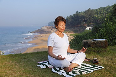 Woman meditating on a meadow above the sea, Bethsaida Hermitage near Kovalam, Kerala, southern India, India, Asia
