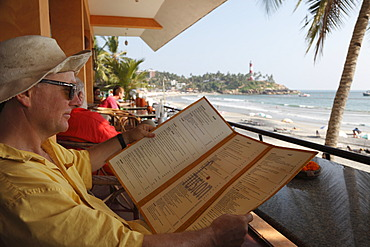 Tourist reading the menu of a cafe on Lighthouse Beach, Kovalam, Malabarian Coast, Malabar, Kerala state, India, Asia