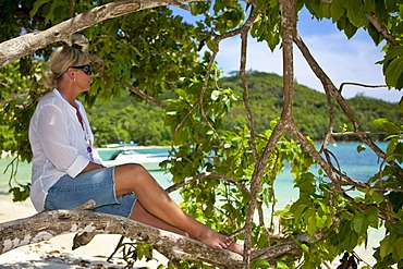 Woman sitting on a tree at the Anse des Anglais and looking at the sea, Mahe Island, Seychelles, Indian Ocean, Africa