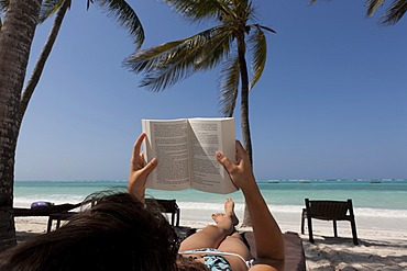 Girl, 16 years, reading a book on the beach under palm trees