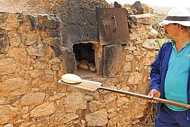 Man baking bread in trditional oven , open-air museum in Tefia , Fuerteventura , Kanarische Inseln