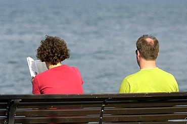 Couple sitting on bench at lake