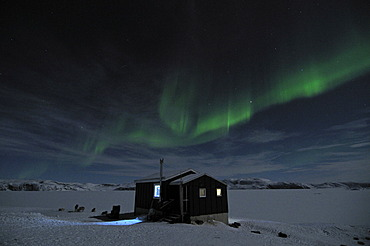Northern lights over a hut in the Ilulissat fjord, Greenland, Arctic North America