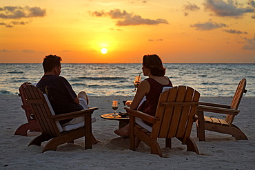 Couple sitting on chairs at the beach with long drinks in front of a golden sundown, Rihiveli, Island, Maldives, South Male Atoll, Archipelago, Indian Ocean, Asia