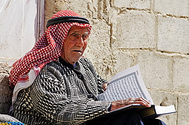 Old man reading a book with Arabic script in the village Djabadin near Maalula, Syria, Middle East, Asia